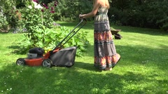 Gardener girl in flip-flop shoes mow lawn with grass cutter in yard. 4K Arkistovideo