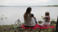 Mother and daughter on the lake on an imaginary fishing. Stock Footage