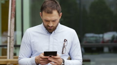 Shy young man using his tablet in the street Stock Footage