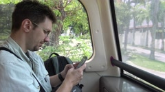 4K Caucasian man in public bus checks his phone at the Singapore city-Dan Stock Footage