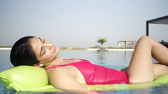Expat woman relaxing on air bed in swimming pool. Stock Footage
