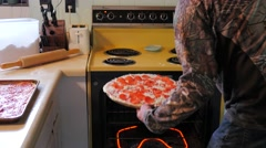 Putting homemade pizza in the oven - stock footage