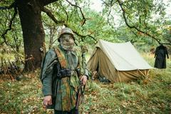 Hidden unidentified re-enactor dressed as World War II german we - stock photo