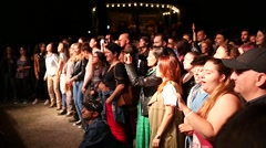 Fan spectators crowd listen to music in front of stage raise hands with phone Stock Footage