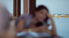 Woman messaging on mobile at poolside. - stock footage