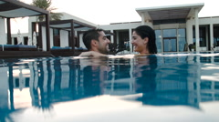 Expat couple embracing in swimming pool. - stock footage