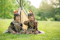 Cute portrait of native american boys with costumes, playing outdoor in the p - stock photo