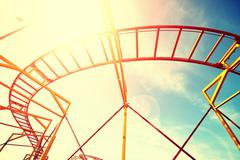 Vintage toned roller coaster rails against sun. Stock Photos