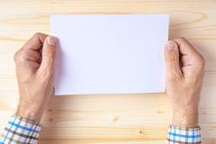 Man holding blank brochure as mock up copy space - stock photo