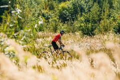 Mountain Bike cyclist riding track in meadow with tall dry  gras Stock Photos