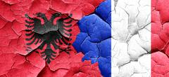 Albania flag with France flag on a grunge cracked wall - stock illustration