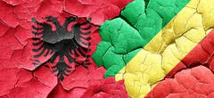 Albania flag with congo flag on a grunge cracked wall - stock illustration