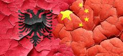Albania flag with China flag on a grunge cracked wall Stock Illustration