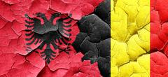 Albania flag with Belgium flag on a grunge cracked wall - stock illustration