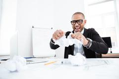 Angry businessman tearing up a document in office - stock photo