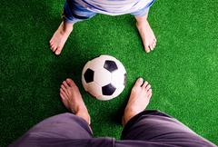 Father and son with soccer ball against green grass - stock photo
