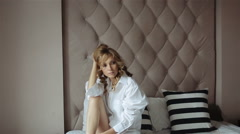 Beautiful Sexy Woman Sitting on White Bed in White Shirt - stock footage