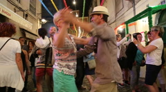 Local man dance with tourist in Lisbon street festival Stock Footage