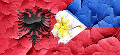 Albania flag with Philippines flag on a grunge cracked wall Stock Illustration