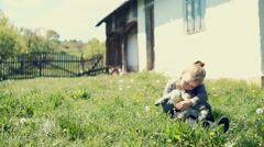 Little girl holding the small goatling. RAW video record - stock footage