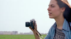 Beautiful young woman taking photos with old film camera. Slow motion Stock Footage