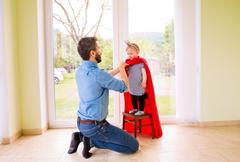 Hipster father with princess daughter in red superhero cape - stock photo