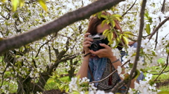 Beautiful young woman taking photos with old film camera of blooming tree. Close Stock Footage