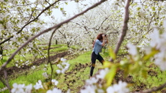Beautiful young woman taking photos with old film camera of blooming tree. Slow Stock Footage