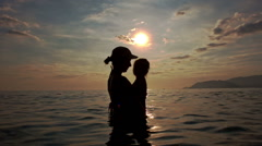 Silhouette of Woman with Toddler in Arms in Sea against Sunset Stock Footage