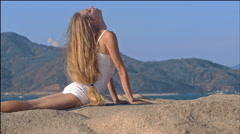 Blond Girl Does Fitness Bends Backward on Large Stone - stock footage