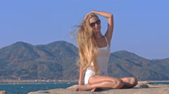 Blond Girl in Top Smoothes Hair Shaken by Wind against Sky - stock footage