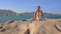 Blond Girl in Top Sits on Rock in Yoga Pose Hands behind Back Stock Footage