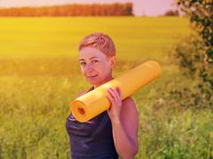 Woman Holding Rolled Up Exercise Mat - stock photo