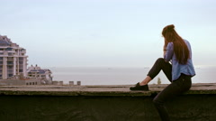 Beautiful young female photographer take photos of cityscape from the roof Stock Footage