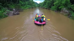 Aerial View - Whitewater rafting boat follow shot down river in Thailand. Stock Footage