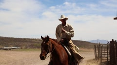 Cowboy riding up to a barn Stock Footage