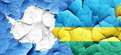 Antarctica flag with rwanda flag on a grunge cracked wall Stock Illustration