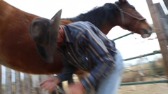 Cowboy cleaning the hooves of a horse (2) - stock footage