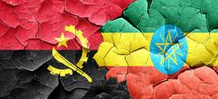 Angola flag with Ethiopia flag on a grunge cracked wall Stock Illustration