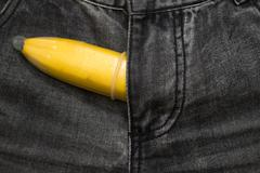 banana fruit in condom inside jeans pants  contraceptive concept - stock photo