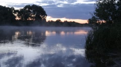 morning sunrise reflection in misty fog rise from flowing river water. - stock footage