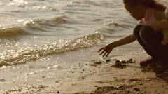 Beautiful little girl 5 years old playing on the beach in the cool weather, buil Stock Footage