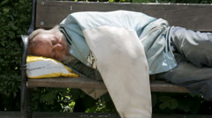 Homeless man sleeping on a bench. Zoom out. Stock Footage
