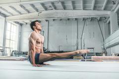 caucasian man gymnastic acrobatics equilibrium posture at gym background - stock photo