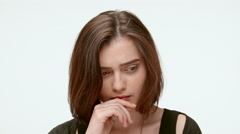 Sad grumpy girl on a white background. Close up. Slow motion Stock Footage