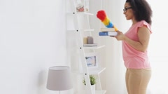 Happy woman with duster cleaning at home Stock Footage