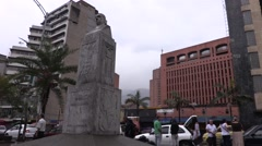 Foot and car traffic behind statue of Pedro Berrio in Parque Berrio Stock Footage