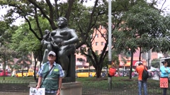 Vendor standing in front of Statue of Motherhood in Plaza Botero Stock Footage