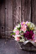 Pastel bouquet from gillyflowers and white alstroemeria in the basket on old, - stock photo