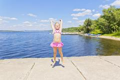 Cute girl on the riverbank in pink swimsuit Stock Photos